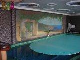 Úszómedence víz alatti redőnyös takaró és üvegmozaik kép dekoráció a háttérben.