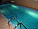 Beltéri, süllyesztett víztükrű üvegmozaik burkolatú vasbeton úszómedence